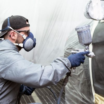 Car painter painting a car door with a mask on, gloves and work clothes