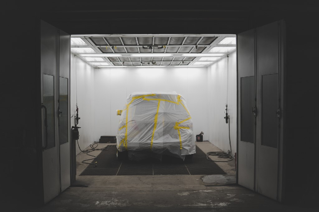 A vehicle covered with a white sheet and yellow tape in a car service garage