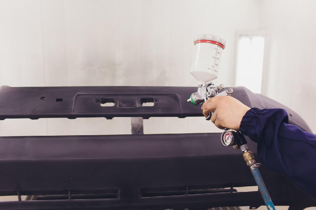 Automotive Paint. Mechanic Painting the Car in Auto Repair Shop
