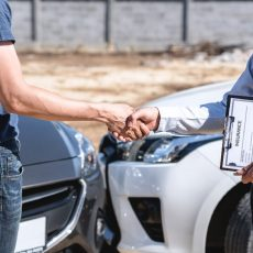 Insurance Agent and customer shaking hands after agreement about in insurance claim, assessed examining car crash, checking and signing on report claim form process after accident collision.